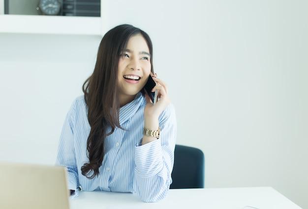 Молодая азиатская бизнес-леди говоря на мобильном телефоне и усмехаясь на ее рабочем месте