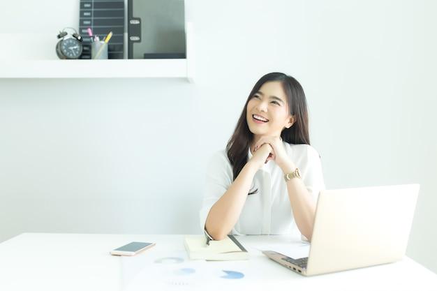 Идея молодой азиатской бизнес-леди усмехаясь и думая о работе на столе в современном офисе.
