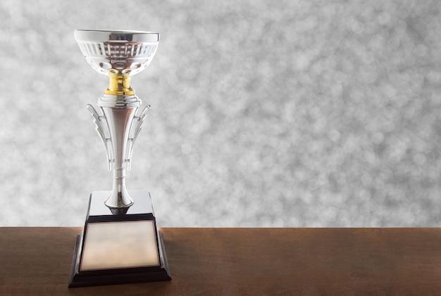 背景のボケ味の木製テーブルの上の銀のトロフィー。コピースペースで賞を受賞。