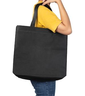 分離された空白の黒い布キャンバスバッグを保持している女性