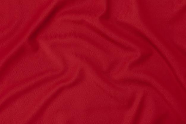 スポーツ服生地テクスチャ背景。赤いサッカーシャツ