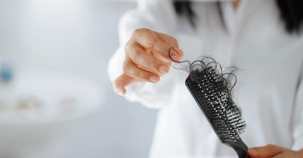 Женщина теряет волосы на расческу в руке