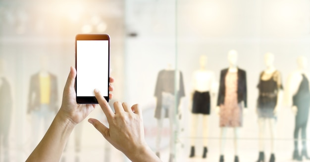 携帯スマートフォンを使用して手を掛け、衣料品店のディスプレイビューで写真を撮る