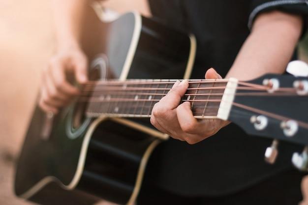アコースティックギターを弾くギタープレイヤー、近づける