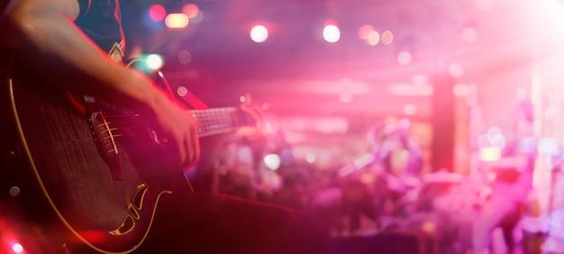 背景、柔らかい、ぼかしのコンセプトのためのステージ上のギタリスト