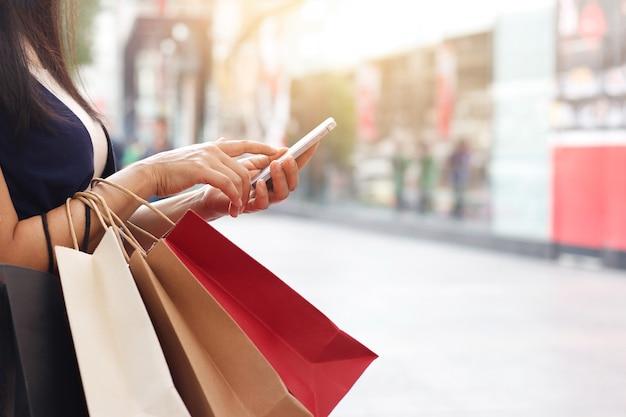 スマートフォンを使用し、ショッピングモールの背景に立っている間、ショッピングバッグを持っている女性