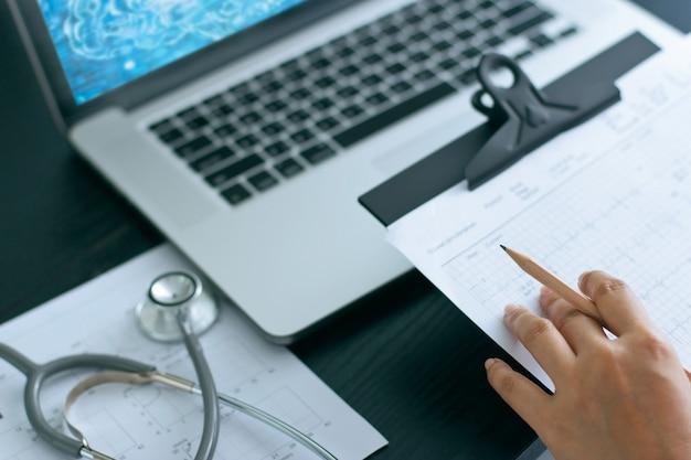 Доктор медицины и стетоскоп на диаграмме отчета, работая с портативным компьютером на больнице.