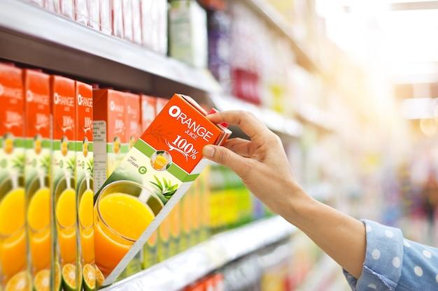 Рука женщины выбирая купить апельсиновый сок на полках в супермаркете