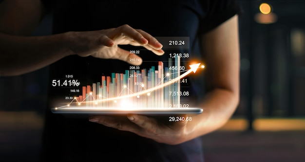 Бизнесмен держа таблетку и показывая растущую виртуальную голограмму статистики, диаграммы и диаграммы с стрелкой вверх