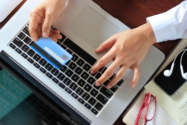 ビジネスの女性が手にクレジットカードでノートパソコンを使用しています。オンライン支払い、銀行取引、ショッピング。