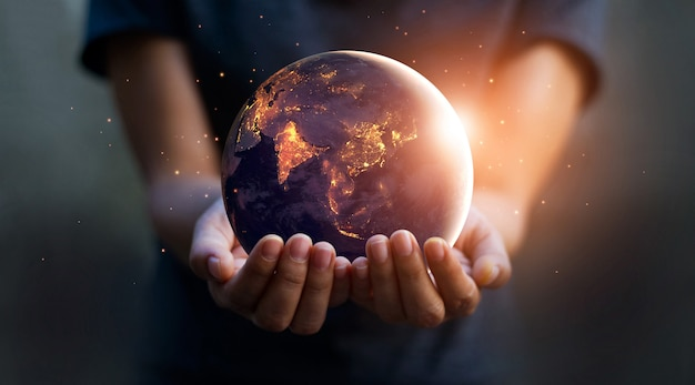 Земля ночью держала в руках человека. день земли. концепция энергосбережения.