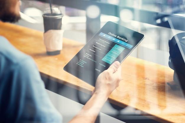 コーヒーショップでタブレット画面デバイスでオンラインバンキングを使用して男の手。
