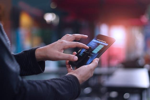 カフェテリアでオンラインバンキングのモバイルスマートフォンを使用している人。
