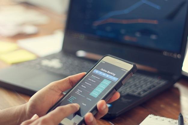 データ情報銀行ネットワーク接続でモバイルのスマートフォンを使用するビジネスマン。