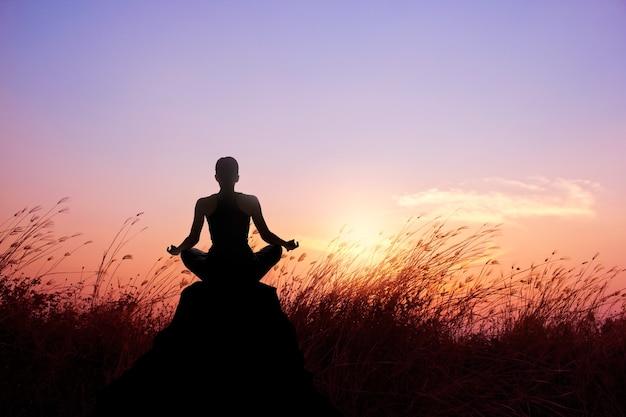 Женщина, практикующих йогу и силуэт медитации на фоне заката природы