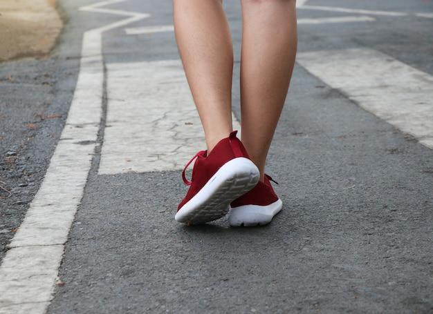人々にとって安全な横断歩道の概念にスポーツの靴を履いて足