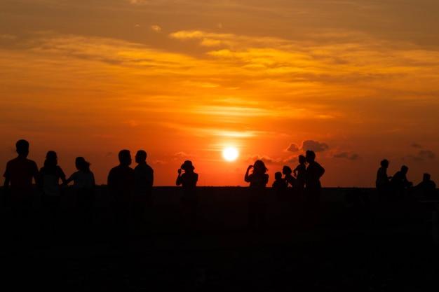 シルエットの人々の活動と夕日