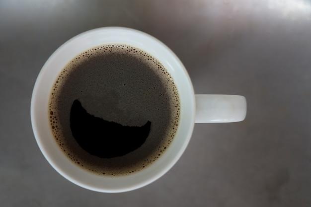 笑顔のシンボルと泡でトップビュー面白いブラックコーヒーは、時間をリラックスできるステンレス製のテーブルに置く