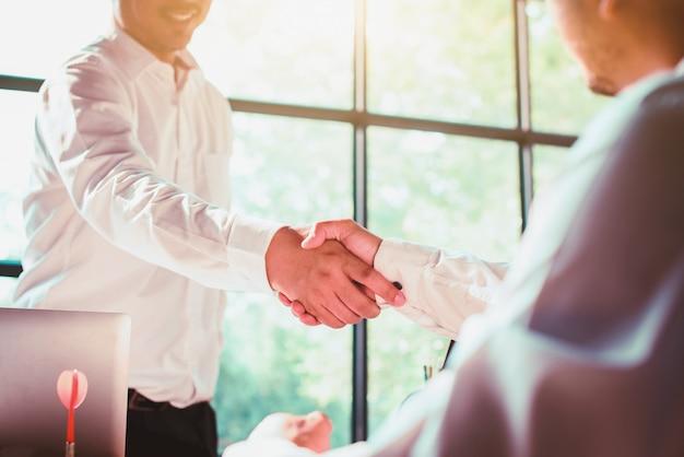 ビジネスマンがオフィスで握手します。