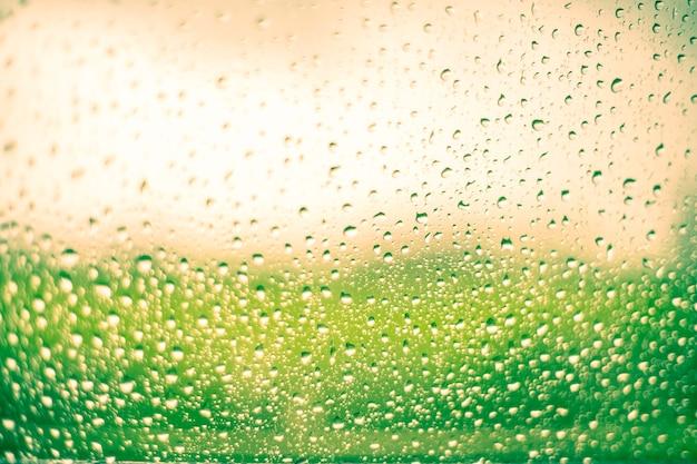 Дождь падает на поверхность оконных стекол с солнечным светом