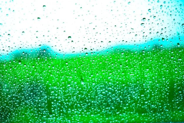 Дождь падает на поверхность оконных стекол с облачным фоном