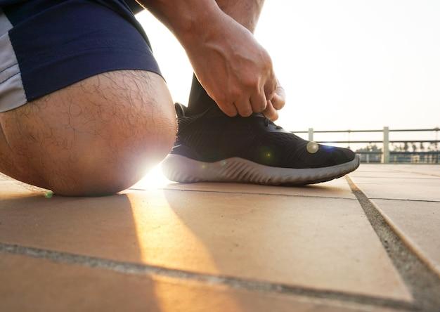 Человек связывает кроссовки
