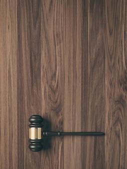 Деревянный молоток судьи на фоне дерева с копией пространства