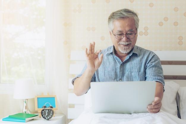 ライフスタイルシニアの男性は、ラップトップコンピュータを使用して親戚への電話