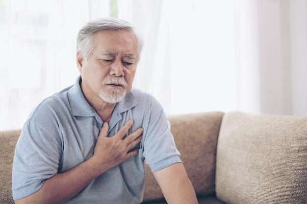 彼の胸の心臓発作の悪い痛みに苦しんでいる高齢男性アジア - 家庭で心配