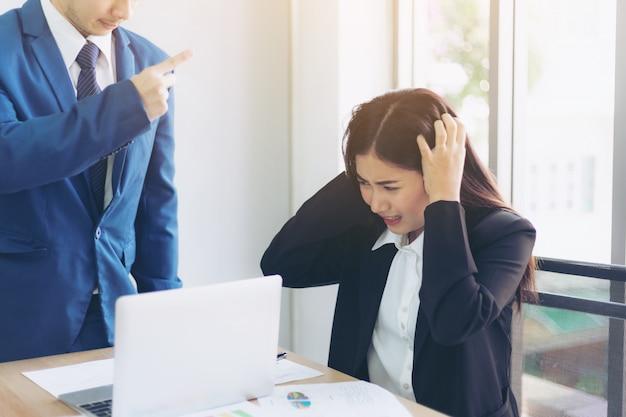 アジアのビジネスの女性の従業員に責任を負う怒っているボスポイントの指