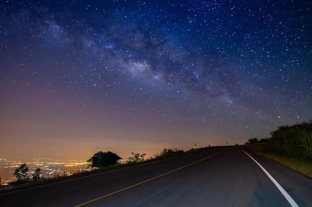山と乳白色の銀河の背景に夜の風景の道路