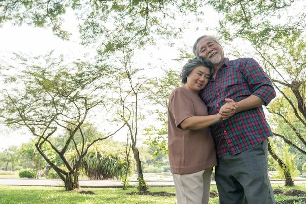 幸せな愛老夫婦、老夫婦の老人と年配の女性が森で抱擁をリラックス