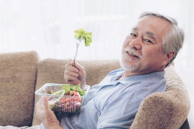 ライフスタイルの年配の男性人はソファーでダイエット食品新鮮なサラダを食べることを幸せに感じる