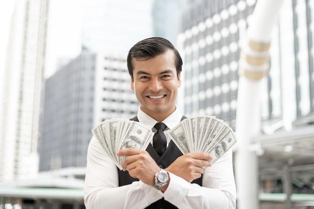 ビジネスの男性の成功ビジネスのためのビジネス地区都市概念にお金米ドル紙幣を保持