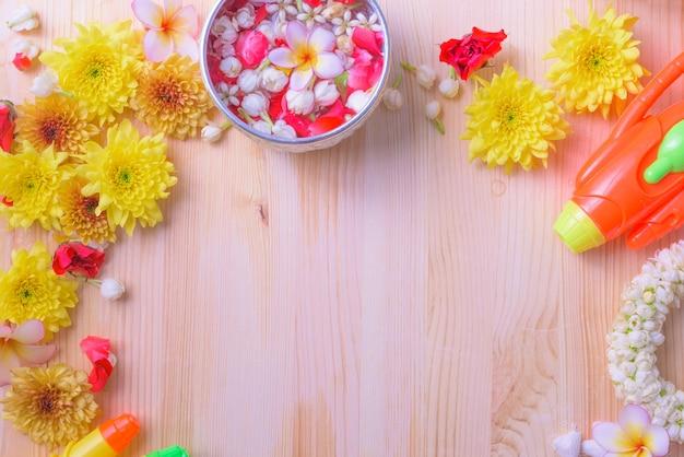ソンクランフェスティバルやタイ新年のための木の背景に花とパイプガン