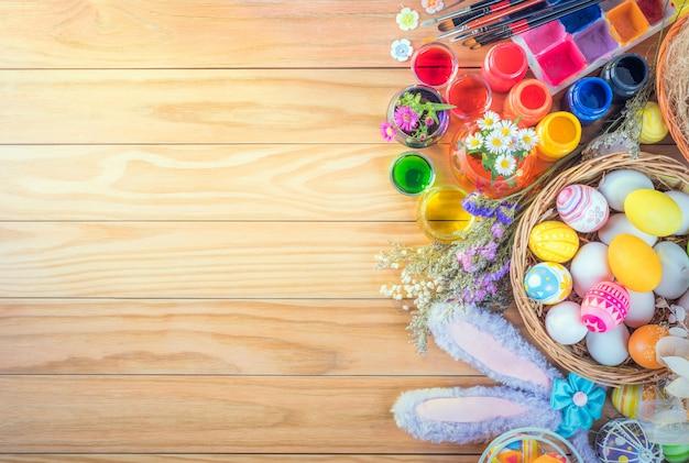 Счастливой пасхи разноцветные яйца и цветок набор пищевых красителей, акриловая кисть для самостоятельной работы на коричневом деревянном полу с копией пространства