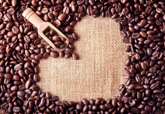 バッグの背景にハートの形として配置されたコーヒー豆のスクープ