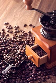 ローストしたコーヒー豆と手動グラインダーをすくい取る