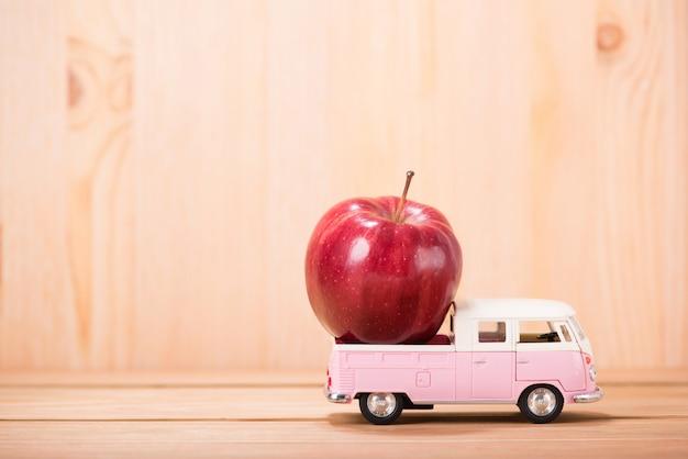 木製の床の背景を持つおもちゃの車の上のリンゴ赤