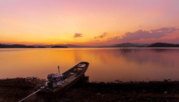 Закат у большого пруда, деревянная лодка припаркована на красивом берегу