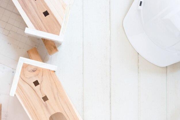 Миниатюрная модель дома с планом плана, белый защитный шлем на белом дереве, копия пространства
