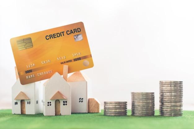 シミュレーション芝生の上のクレジットカードとお金のコインスタックを持つミニチュアの家モデル