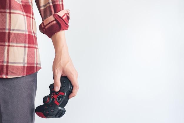 若い男性がジョイスティックのゲームパッドを持っている赤いスコットパターンシャツ手