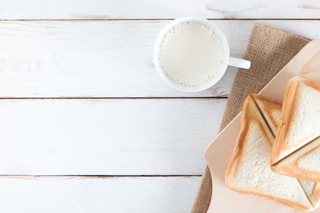 焼きたてのパンと白の木製テーブルの上の白いカップに熱いミルクをスライスしたパンの上から見た画像、朝の朝食、新鮮な自家製、コピースペース