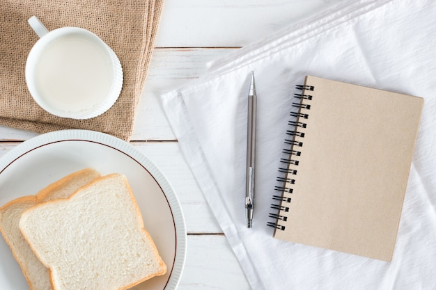 Изображение вида сверху нарезанного хлеба на блюде с горячим молоком, карандашом и коричневой бумажной записной книжкой на белом деревянном столе, завтрак по утрам, свежие домашние, копия пространства