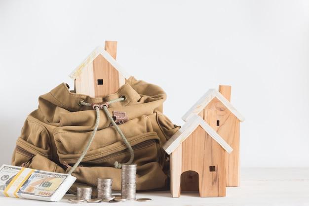 Миниатюрная модель дома в коричневом цветном рюкзаке и рядом с ней купюры, денежные монеты