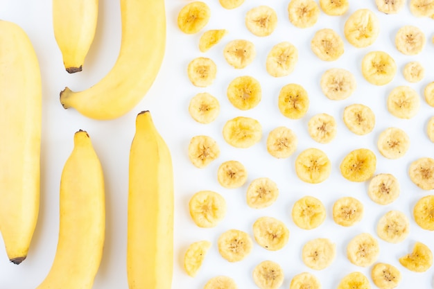 Банан с кучей сушеных бананов ломтиками полного пространства, изолированных на белом
