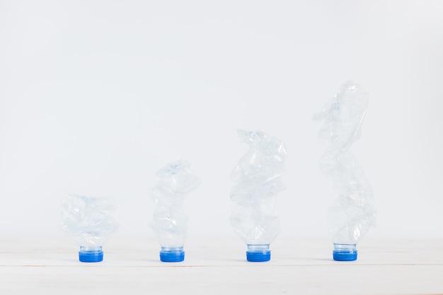 Мусор утилизировать пластиковые бутылки на белой деревянной доске от низкого до высокого, решение глобального потепления.