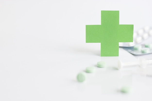 Зеленый медицинский крест символ и шприц с таблеткой на белом фоне.