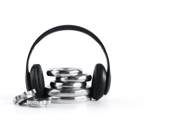 白で隔離されるワイヤレスヘッドフォンとクロムプレートダンベル